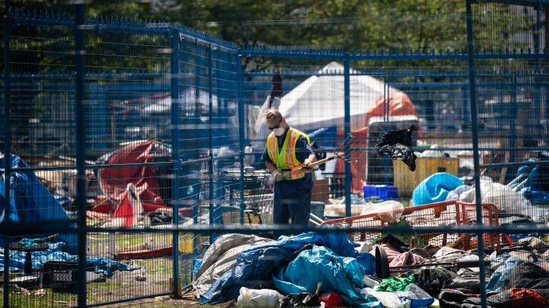 A city worker picks through belongings left behind at a homeless camp at Oppenheimer Park after a 12 p.m. deadline for the park to be vacated, in the Downtown Eastside of Vancouver, on Saturday, May 9, 2020. The province is temporarily relocating hundreds of people from tent encampments in Vancouver and Victoria to hotel and community centre accommodations to protect them from the ongoing COVID-19 pandemic. THE CANADIAN PRESS/Darryl Dyck