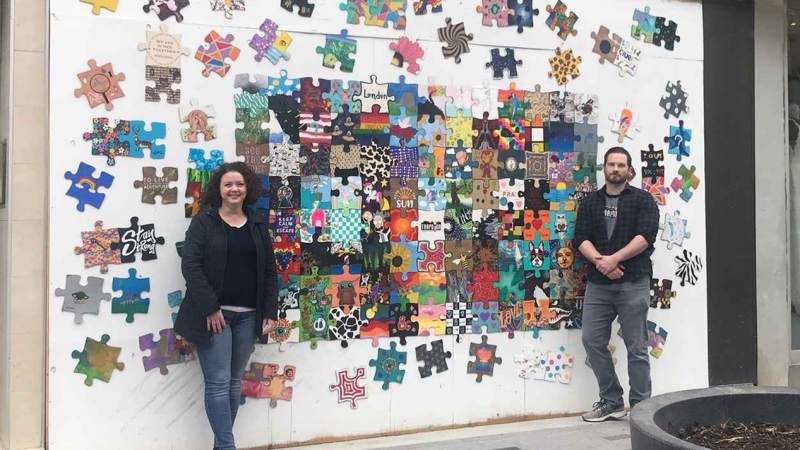 Valerie Charlebois and Derek Noon of Trapdoor London stand in front of the puzzle painted by the community. (Reta Ismail / CTV News)