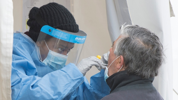 A health-care worker swabs a man at a walk-in COVID-19 test clinic in Montreal North, Sunday, May 10, 2020, as the COVID-19 pandemic continues in Canada and around the world. (THE CANADIAN PRESS/Graham Hughes)