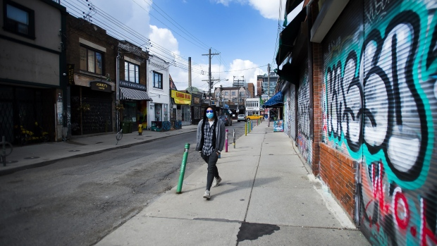 A lone person walks past closed businesses in Kensington Market in Toronto on Wednesday, April 15, 2020. THE CANADIAN PRESS/Nathan Denette