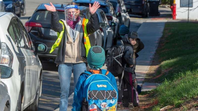 Teacher Janick Mille welcomes students at Ecole Marie Rose as elementary schools outside the greater Montreal area reopen Monday May 11, 2020 in Saint Sauveur, Que.. Schools and daycare centers have been closed due to the COVID-19 pandemic. THE CANADIAN PRESS/Ryan Remiorz