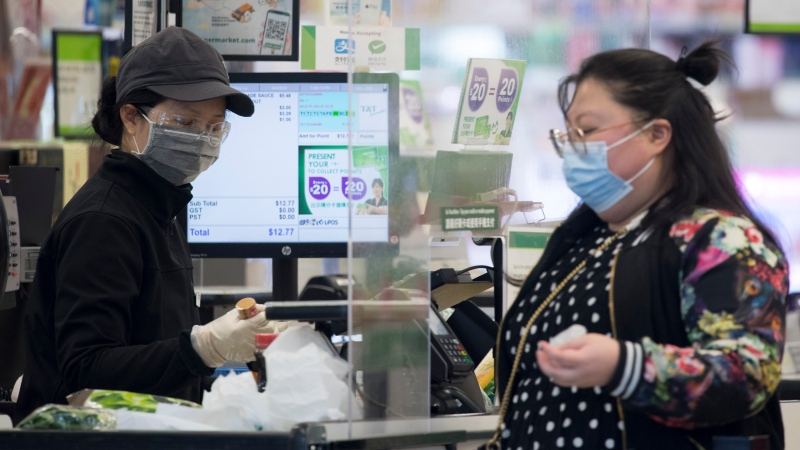 A grocery store worker wears a protective face mask and gloves as a customer stands on the other side of the plexiglass divider in downtown Vancouver Wednesday, April 29, 2020. THE CANADIAN PRESS/Jonathan Hayward