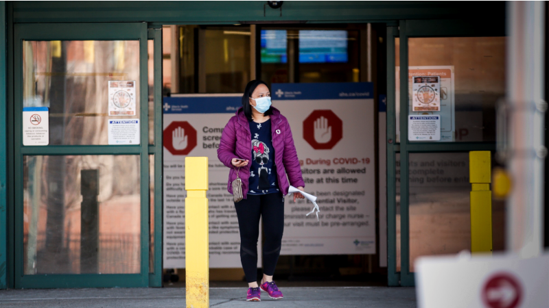 A woman leaves the Peter Lougheed Centre hospital in Calgary, Alta., Thursday, April 9, 2020, essential visitors are the only visitors permitted in Alberta hospitals as part of COVID-19 precautions. THE CANADIAN PRESS/Jeff McIntosh​