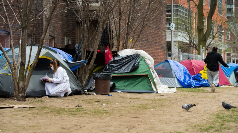 In this file photo, a worker from Sanctuary, a christian charitable organization, tends to homeless people in their tents during the COVID-19 pandemic in Toronto on Tuesday, April 28, 2020. THE CANADIAN PRESS/Nathan Denette
