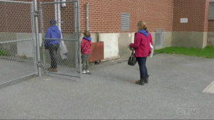 Children line up at a distance from each other before entering their school.