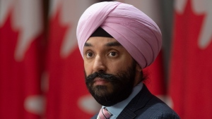 Innovation, Science and Industry Minister Navdeep Bains watches Minister of Finance Bill Morneau appear on a large screen during a news conference Friday April 24, 2020 in Ottawa. THE CANADIAN PRESS/Adrian Wyld
