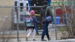A woman walks her daughter to school Monday May 11, 2020 in Gatineau, Quebec. (THE CANADIAN PRESS/Adrian Wyld)