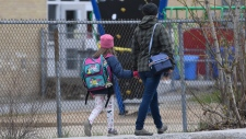 A woman walks her daughter to school Monday May 11, 2020 in Gatineau, Quebec. THE CANADIAN PRESS/Adrian Wyld
