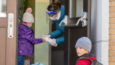 Students get their hands sanitized as they enter Ecole Marie Rose as elementary schools outside the greater Montreal area reopen Monday May 11, 2020 in Saint Sauveur, Que. THE CANADIAN PRESS/Ryan Remiorz
