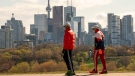 Two men in masks walk in the late afternoon sun in Toronto on Thursday, May 7, 2020. With warmer weather set to return physical distancing in public spaces will become more difficult. THE CANADIAN PRESS/Frank Gunn
