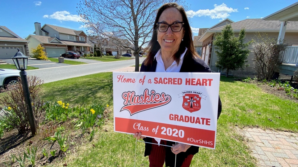 Sacred Heart vice principal Mary Jane Gillier-Symes with a lawn sign for graduating students. Stittsville, ON. May 13, 2020. (Tyler Fleming / CTV News)