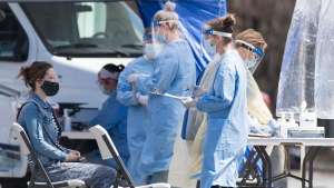 A woman waits to be tested for COVID-19 at a mobile test clinic in the Montreal neighbourhood of Saint-Michel, Sunday, May 3, 2020, as the COVID-19 pandemic continues in Canada and around the world. THE CANADIAN PRESS/Graham Hughes