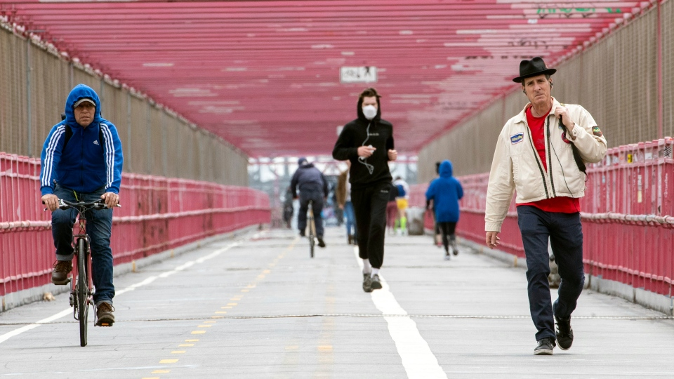 In this Monday, May 11, 2020 photo, a jogger wearing a face masks runs in between a biker and a pedestrian not wearing masks as they make their way over the Williamsburg bridge in New York. (AP Photo/Mary Altaffer)