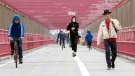 In this Monday, May 11, 2020 photo, a jogger wearing a face masks runs in between a biker and a pedestrian not wearing masks as they make their way over the Williamsburg bridge in New York.New York's governor has ordered masks for anyone out in public who can't stay at least six feet away from other people. Yet, while the rule is clear, New Yorkers have adopted their own interpretation of exactly when masks are required, especially outdoors. (AP Photo/Mary Altaffer)