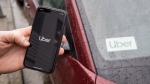 The Uber app is seen on an iPhone near a driver's vehicle after the company launched service, in Vancouver, Friday, Jan. 24, 2020. Uber Technologies Inc. drivers, couriers and passengers in Canada will be required to wear a mask starting Monday. THE CANADIAN PRESS/Darryl Dyck