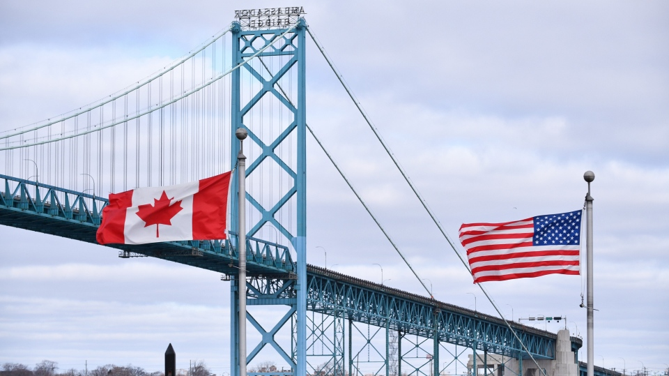 Canadian and American flags fly near the Ambassador Bridge at the Canada-USA border crossing in Windsor, Ont. on Saturday, March 21, 2020. (THE CANADIAN PRESS/Rob Gurdebeke)