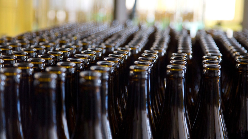In this Thursday, May 26, 2016 file photo, empty beer bottles wait to be cleaned and filled at a bottling plant in Bruges, Belgium. (AP Photo/Virginia Mayo, File)