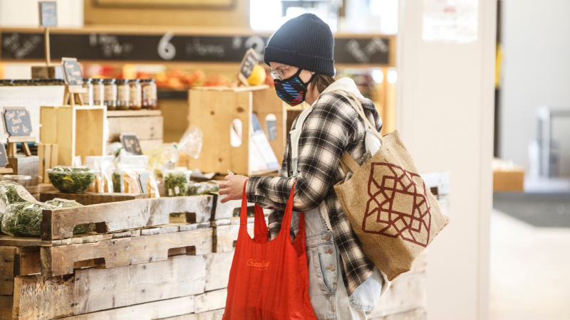 A shopper wearing a mask buys groceries at a sparse farmers market Edmonton as people stay in doors to protect against getting the COVID-19 virus, in Edmonton on Sunday March 22, 2020. THE CANADIAN PRESS/Jason Franson