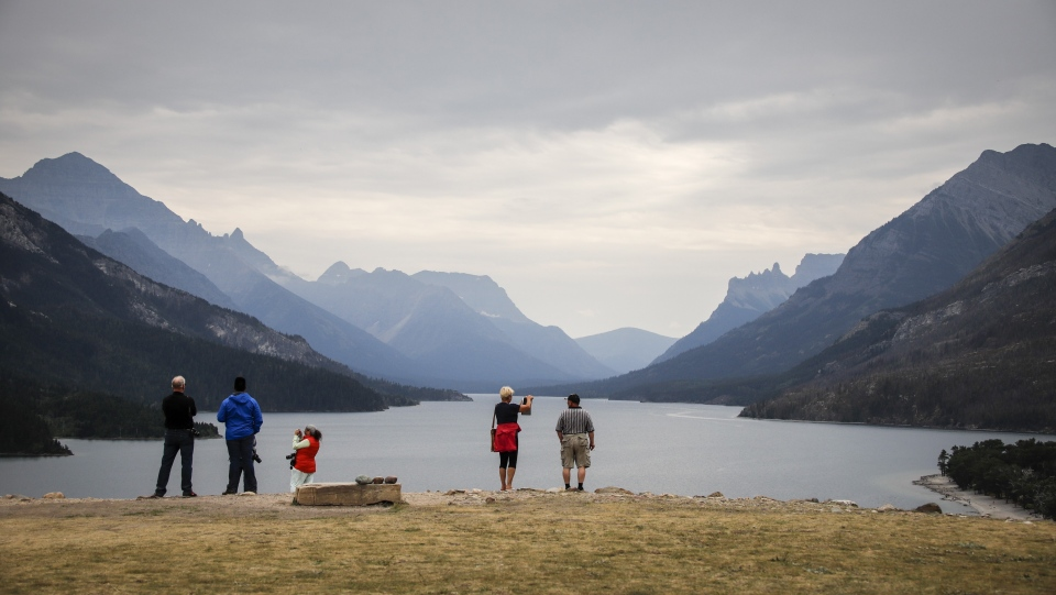 Tourists look out over Waterton Lake after a wildfire two years ago in Waterton National Park, Alta., August 9, 2019. THE CANADIAN PRESS/Jeff McIntosh