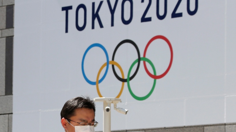 FILE - In this March 25, 2020, file photo, a man walks in front of a Tokyo Olympics logo at the Tokyo metropolitan government headquarters building in Tokyo. (AP Photo/Koji Sasahara, File)