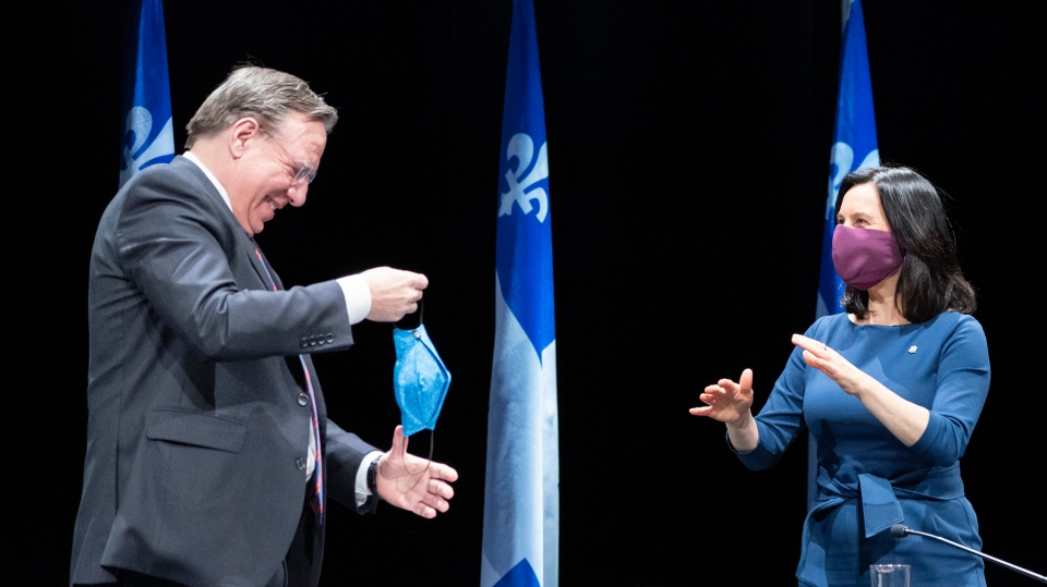 Quebec Premier Francois Legault is told to slip on his protective mask by Montreal Mayor Valerie Plante following a news conference in Montreal, on Thursday, May 14, 2020. THE CANADIAN PRESS/Paul Chiasson