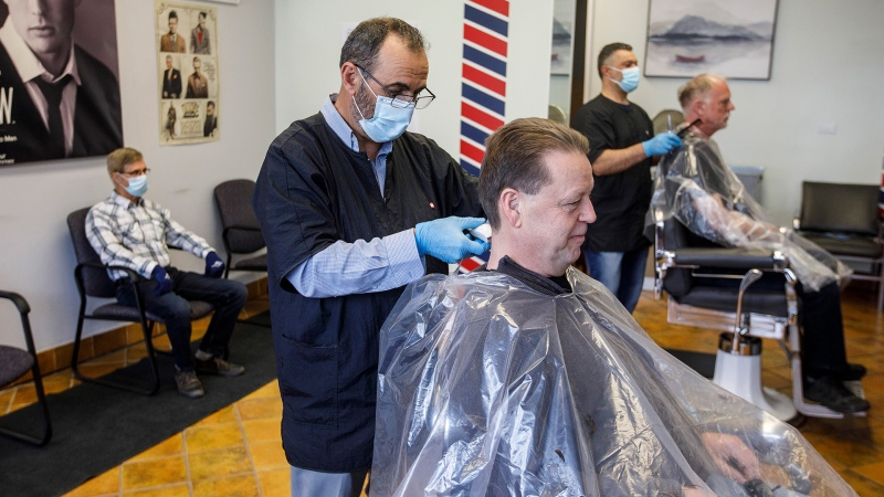 Customers get their hair cut by barbers Ted Alkadri, left and Billy Salla at Universal Barber Shop as businesses reopen during the COVID-19 pandemic, in Edmonton on Thursday May 14, 2020. THE CANADIAN PRESS/Jason Franson