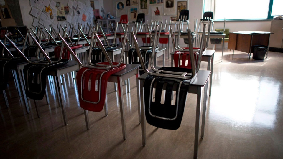 A vacant teachers desk is pictured at the front of a empty classroom is pictured at McGee Secondary school in Vancouver, B.C. Friday, Sept. 5, 2014. The Manitoba government says it is closing schools for three weeks because of COVID-19. Education Minister Kelvin Goertzen says classes will be suspended starting Monday. THE CANADIAN PRESS/Jonathan Hayward