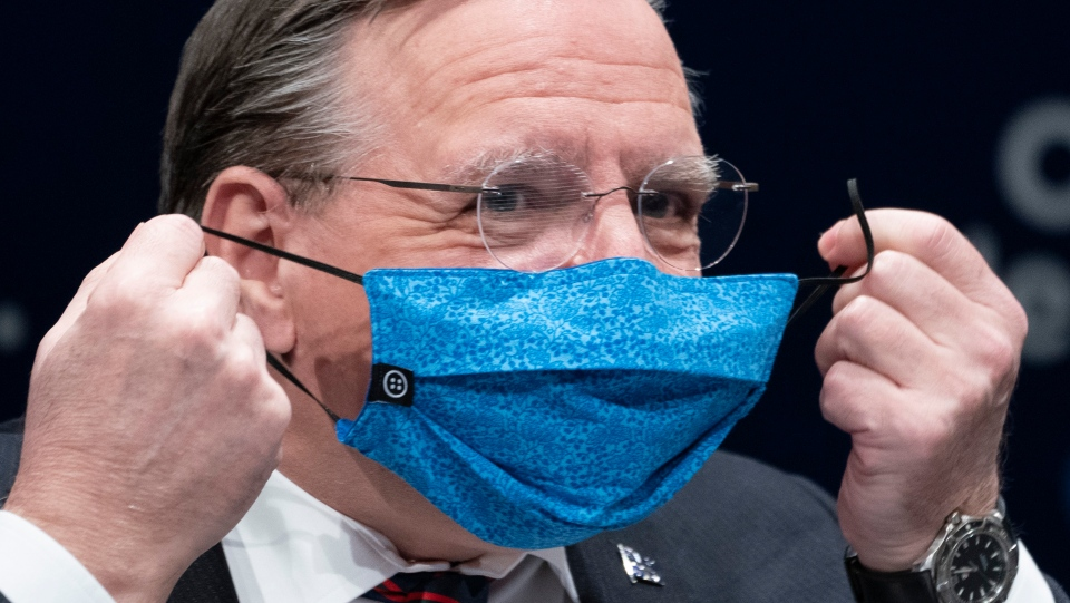 Francois Legault removes his protective mask
