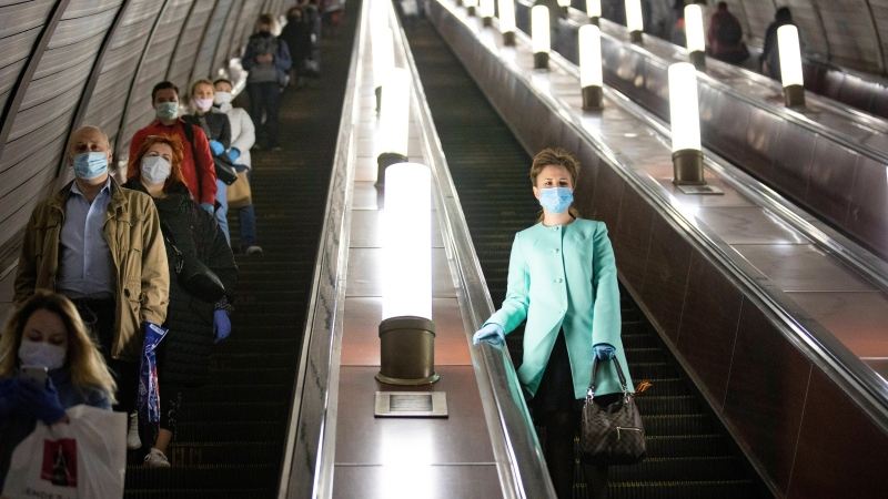 People wearing face masks and gloves to protect against coronavirus, observe social distancing guidelines as they go down the subway on the escalator in Moscow, Russia, Tuesday, May 12, 2020. (AP Photo/Alexander Zemlianichenko)