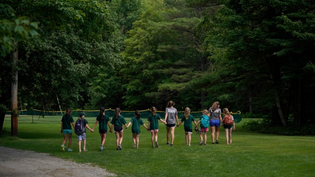 In this undated photo released by Camp Walt Whitman, campers walk across a field at Camp Walt Whitman, a sleepaway camp in the White Mountains of New Hampshire. (Camp Walt Whitman via AP)