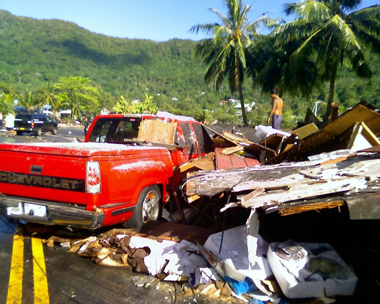A pickup truck lies under a pile of rubble from a business structure in Pago Pago, American Samoa after tsunami waves swept ashore early Tuesday, Sept. 29, 2009. (AP / Ardie Roque)