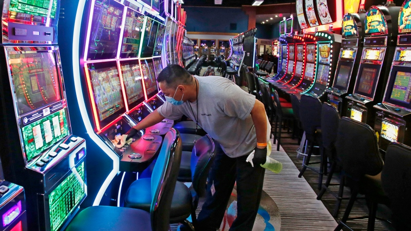 Tobias Morales disinfects gaming machines in preparation for the reopening of Lucky Star Casino after a temporary shutdown due to coronavirus concerns, Friday, May 15, 2020, in Concho, Okla. Employees are required to wear facial coverings while facial coverings are encouraged for casino guests. (AP Photo/Sue Ogrocki)