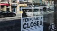 Storefronts in Ottawa's Glebe neighbourhood are reflected in a sign indicating the temporary closure of a business to prevent the spread of COVID-19, on Tuesday, March 24, 2020. (THE CANADIAN PRESS / Justin Tang)
