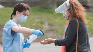 A health-care worker sprays disinfectant on a woman's hands at a mobile COVID-19 testing clinic in Montreal, Sunday, May 17, 2020, as the COVID-19 pandemic continues in Canada and around the world. THE CANADIAN PRESS/Graham Hughes