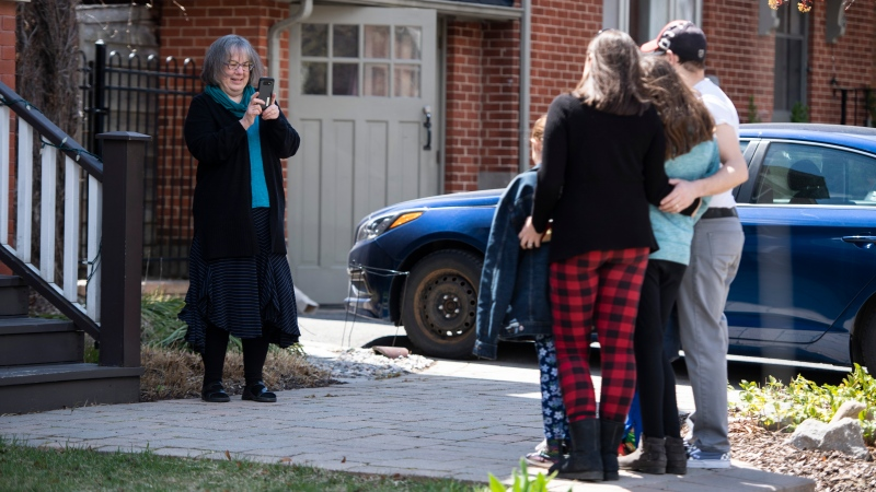 Elizabeth MacMillan takes a photo of her family, daughter Carolynn Landry, son-in-law Kevin, and grandchildren Zoe, Gemma and Jacob, as they celebrate Mother's Day at a distance in Ottawa, in the midst of the COVID-19 pandemic on Sunday, May 10, 2020. THE CANADIAN PRESS/Justin Tang