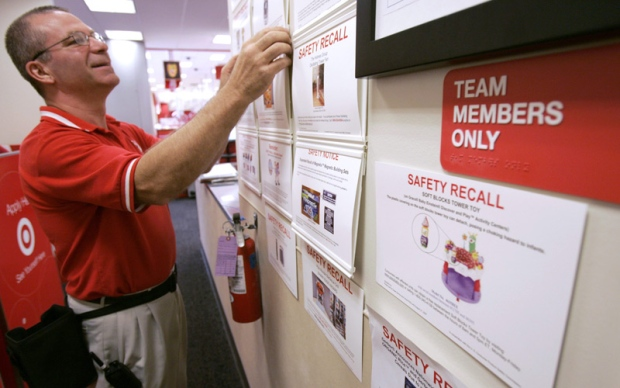 Target employee Bruce Noll adjusts safety recall notices on a bulletin board at a Target store in Richmond, Va., Tuesday, Aug. 14, 2007.  (AP / Steve Helber)