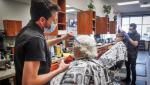 Barber Salim Alhaj, cuts the hair of client, John Gee, of Calgary, who came to the Kingsview Barbershop on its re-opening in Airdrie, Alta., Thursday, May 14, 2020, amid a worldwide COVID-19 pandemic. THE CANADIAN PRESS/Jeff McIntosh