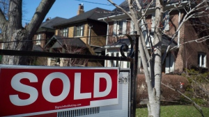 A sold sign is shown in front of west-end Toronto homes Sunday, April 9, 2017. (Graeme Roy / THE CANADIAN PRESS)