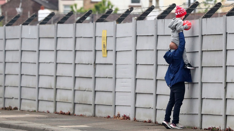 A man holds a child up over a fence to look into Liverpool's Melwood training ground after the English Premier League announced soccer players can return to training in small groups as the coronavirus lockdown was eased starting today Tuesday May 19, 2020. (Peter Byrne/PA via AP)