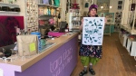 Tara Davis, owner of Tara Davis Studio Boutique, shows off a Winnipeg tea towel.  She expects an extension, banning non-essential travel between Canada and the United States will have an effect on her business. (Source: Josh Crabb/ CTV News Winnipeg)