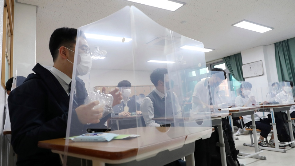 Senior students wait for a class to begin with plastic shields placed on their desks at Jeonmin High School in Daejeon, South Korea, Wednesday, May 20, 2020. (Kim Jun-beom/Yonhap via AP)