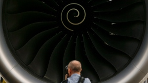 A visitor takes a photo of the Rolls-Royce jet engine of the Airbus A350-1000 parked at the static display area during the Singapore Airshow on Feb. 7, 2018, in Singapore. (Yong Teck Lim / AP)
