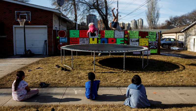 A family sets up a trampoline with a message of hope on a wall in their yard, during the COVID-19 pandemic, in Edmonton on Thursday, April 16, 2020. THE CANADIAN PRESS/Jason Franson