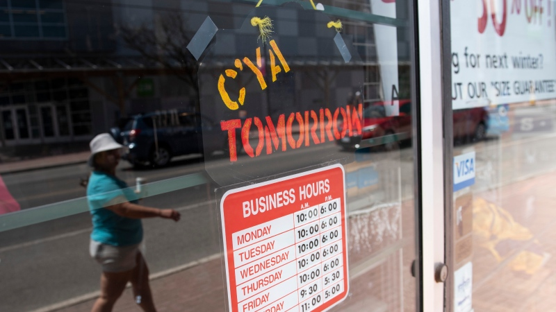 A sign on a closed shop welcomes shoppers to return tomorrow, in Ottawa, on May 18, 2020. (Justin Tang / THE CANADIAN PRESS)