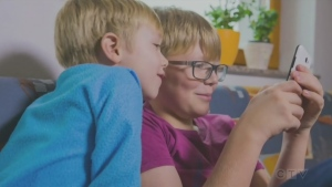Two kids look at a smartphone