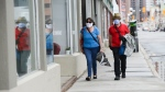 A couple wear masks while out for a walk in downtown Ottawa during the COVID-19 pandemic on Friday, May 1, 2020. (THE CANADIAN PRESS / Sean Kilpatrick)