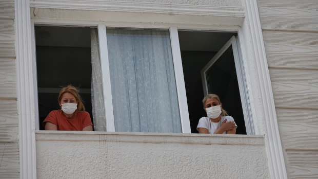 In this May 15, 2020 photo, a woman who had been experiencing COVID-19 symptoms looks from her window in Istanbul. (AP Photo/Emrah Gurel)