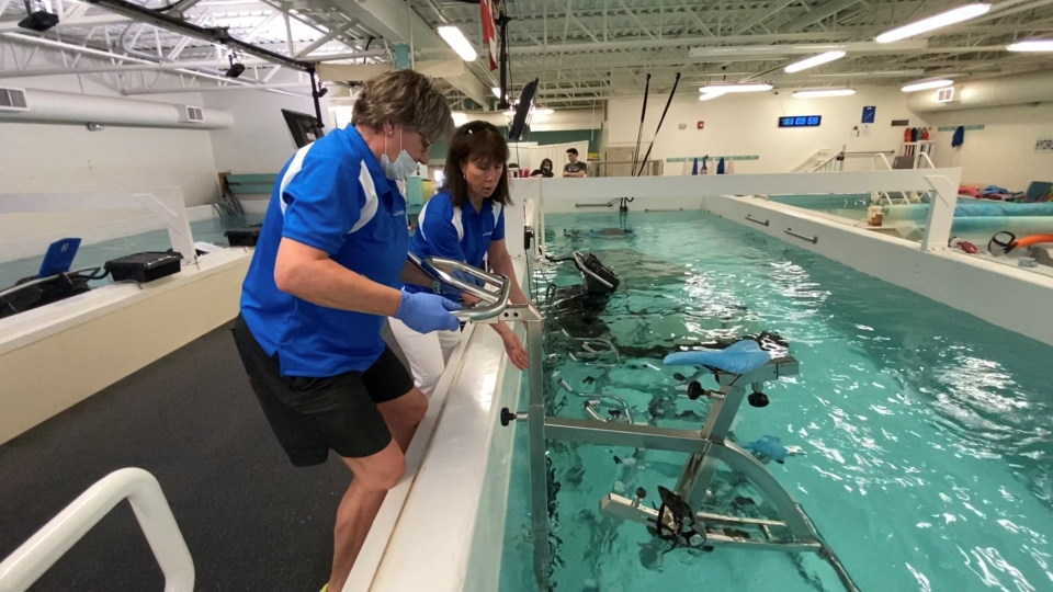 LiquidGym co-owner Karen Snyder, and Dawna Ramsay removing an underwater spin bike for delivery to clients home. Ottawa, ON. May 20, 2020. (Tyler Fleming / CTV News Ottawa)