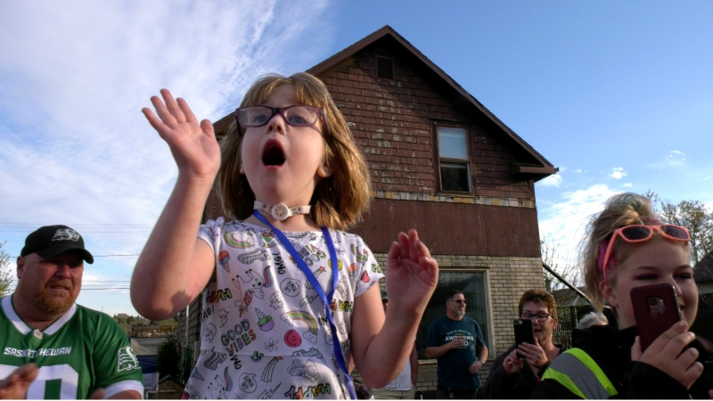 Five-year-old Kendrah waves as a parade passes by celebrating her release from hospital.
