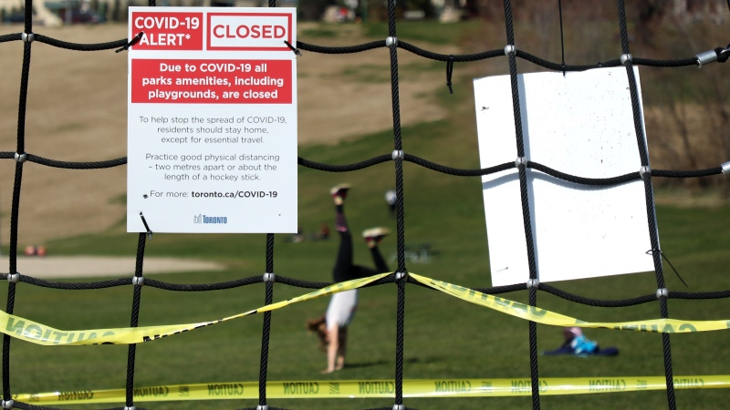 A girl tries a handstand in a Toronto park near a playground closed due to the COVID-19 pandemic on Monday, April 6, 2020. THE CANADIAN PRESS/Colin Perkel
